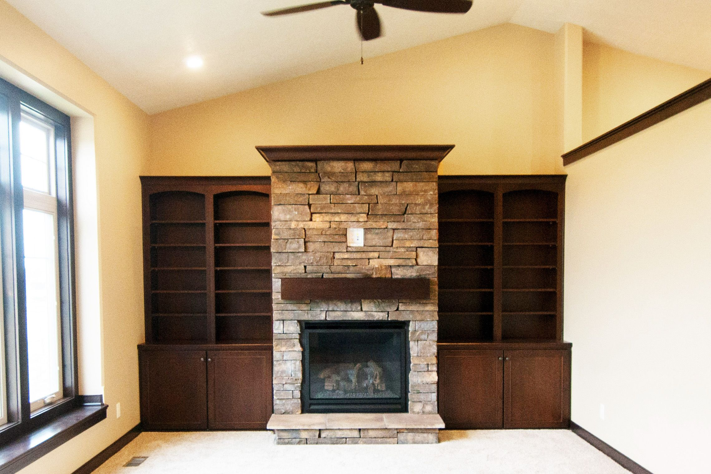 Stone fireplace in living room with built in
