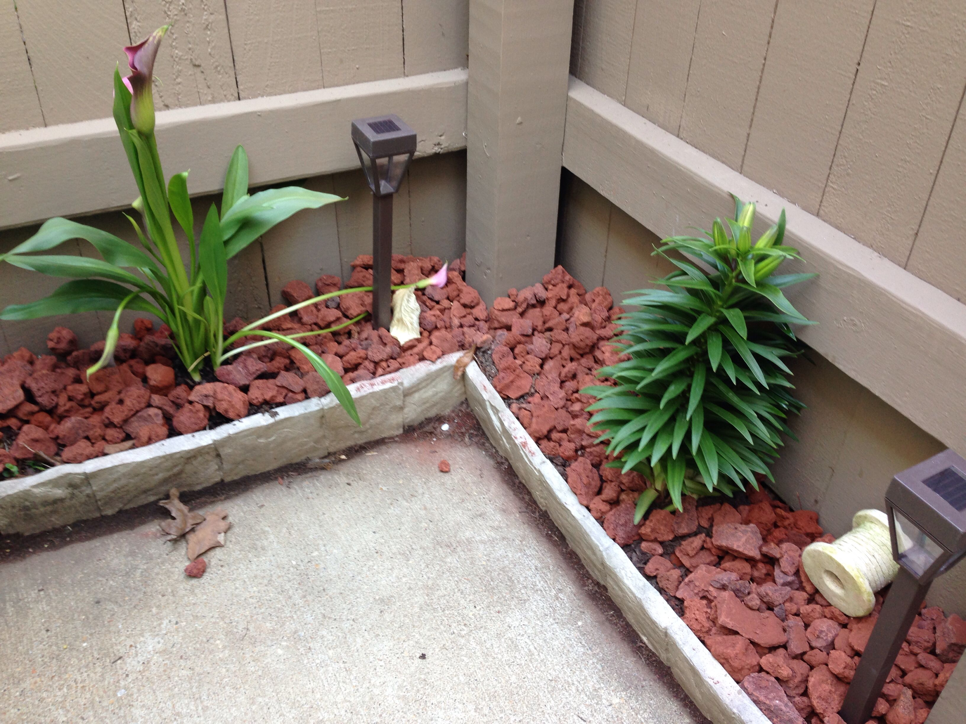 small fenced in condo patio border with red lava rock and solar lights