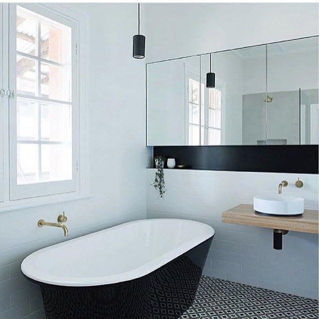 Minimalist bathroom with black stand alone bath tub with gold taps ...