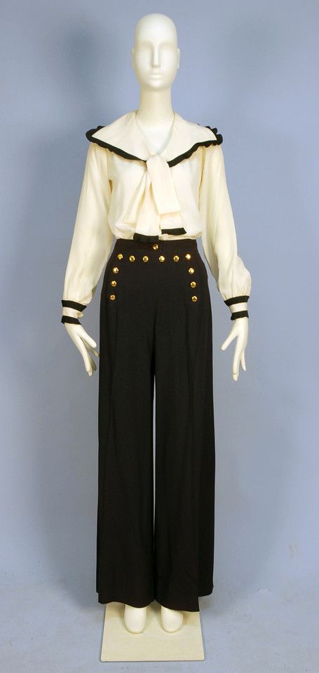 Blouse and Sailor Pants by Yves Saint Laurent Rive Gauche, 1970's. Cream silk blouse having wide collar with tie and cuff trimmed in pleated navy silk, navy wide leg high waisted fall front trousers with brass buttons, labeled.