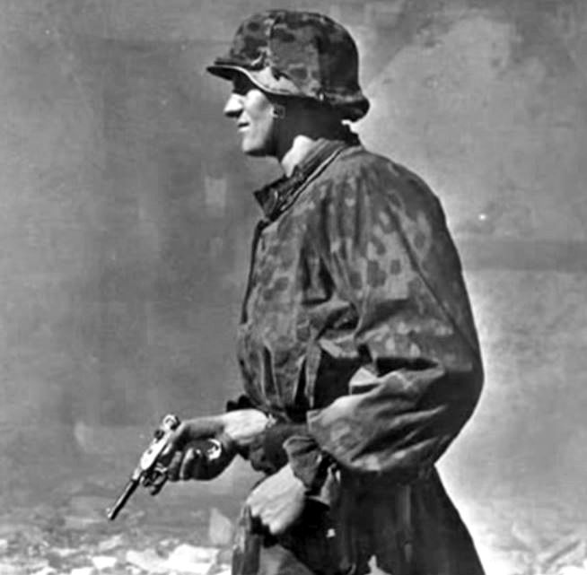 "Waffen SS man with Luger 9mm pistol. He is wearing the standard issue camouflage tunic and helmet of the ""Erbsenmuster"" (Pea pattern) variety introduced in early 1944. Collectors call this pattern the ""44 Dot""."