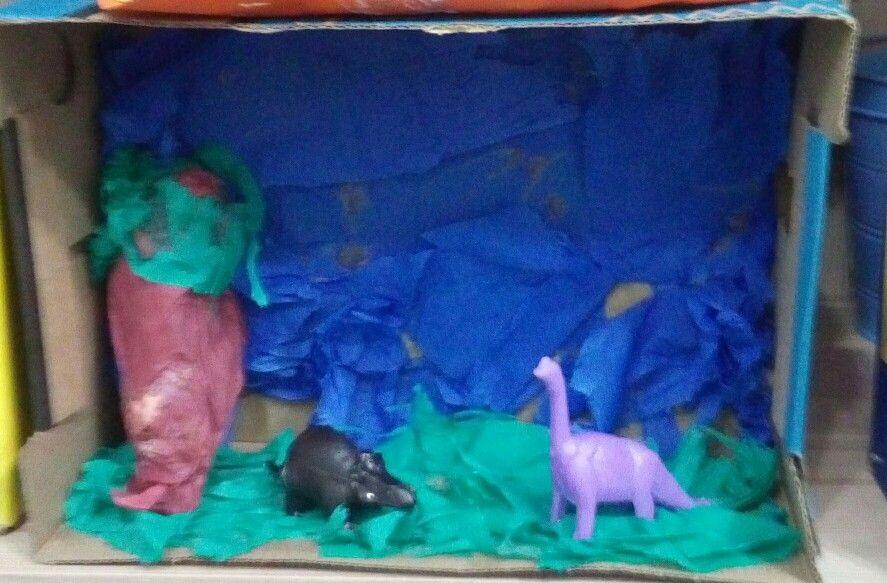 """Maquete """"Na era dos dinossauros"""" com colagem de papel crepom, árvore de jornal e colagem de pequenos dinossauros de brinquedo."""