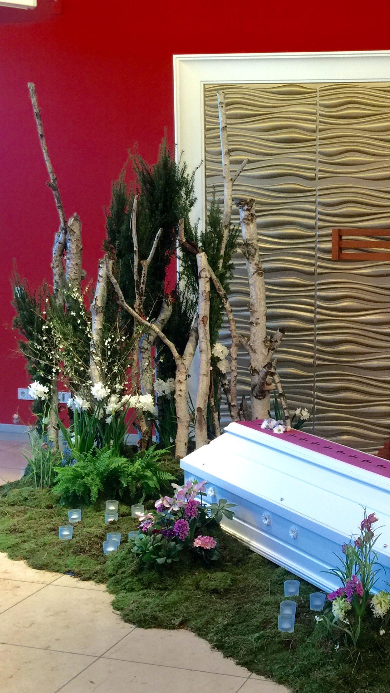 Sargschmuck - betonierte Birkenstämme und Frühlingsblumen auf Moos