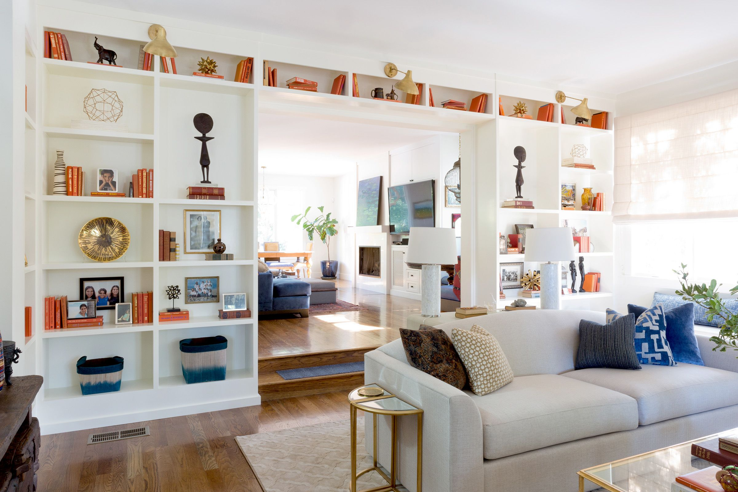 Large, open, clean, white living room with orange bookshelf accents ...