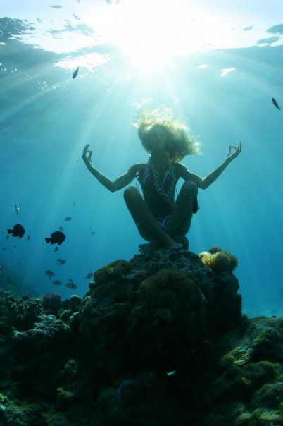 Om. An inspirational photo of a girl underwater, almost dream-like surrounding with a halo of sunlight shining upon her with free-flowing hair...letting go of inhibitions, mediating for peace.