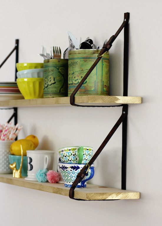 Our DIY wooden shelf with belt straps...also, we store our silverware in coffee  tea cans for easy access.