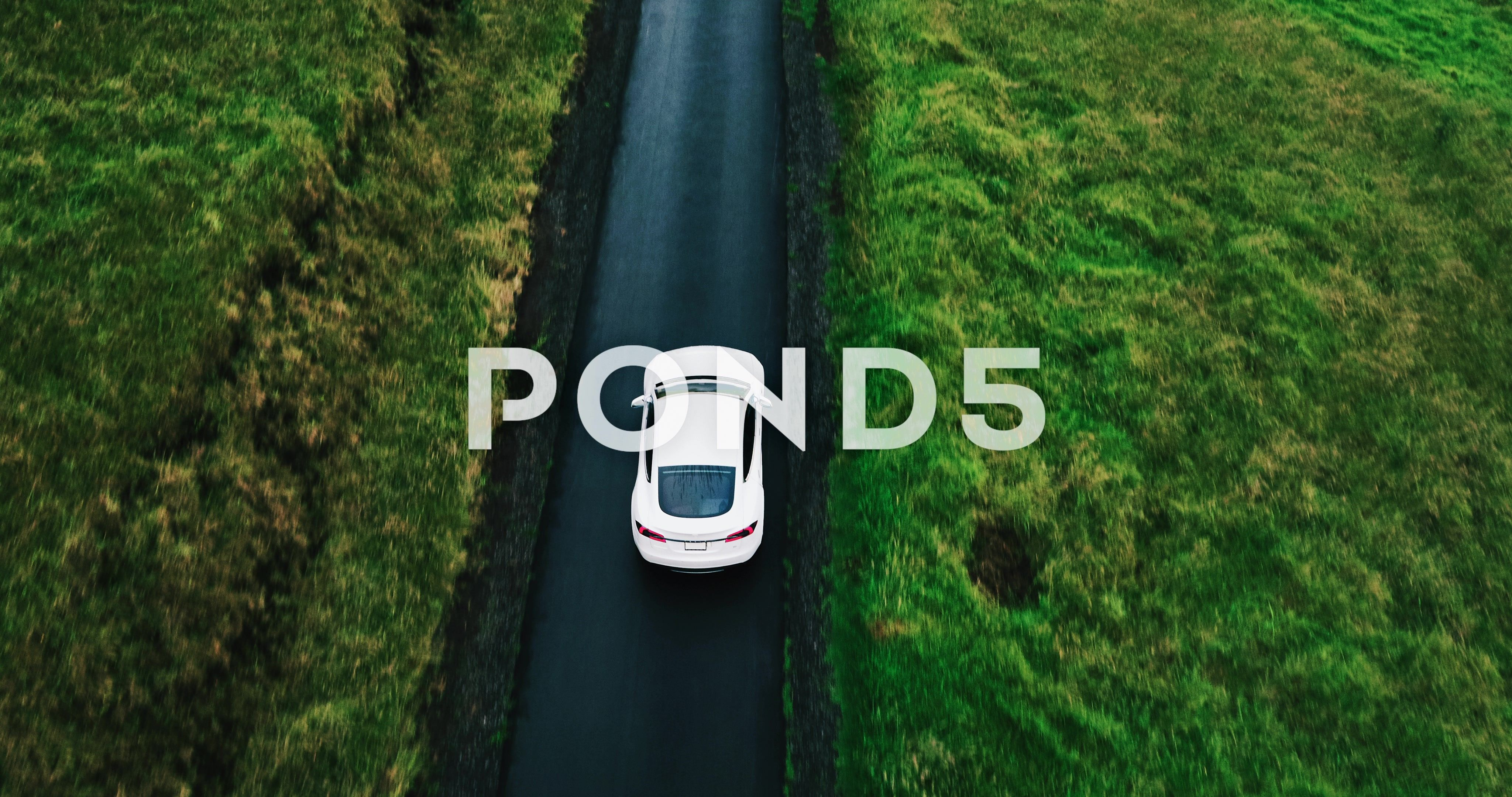 Aerial view electric car driving on country road Stock