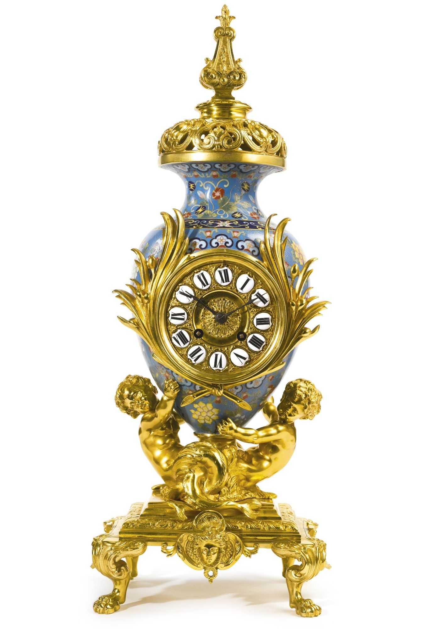 A GILT BRONZE AND CLOISONNÉ ENAMEL MANTEL CLOCK FRANCE, LATE 19TH/EARLY 20TH CENTURY cast with a pair of young tritons holding aloft a Chinese-style vase centered by a clock dial, the twin train movement with the JAPY seal and numbered 2002