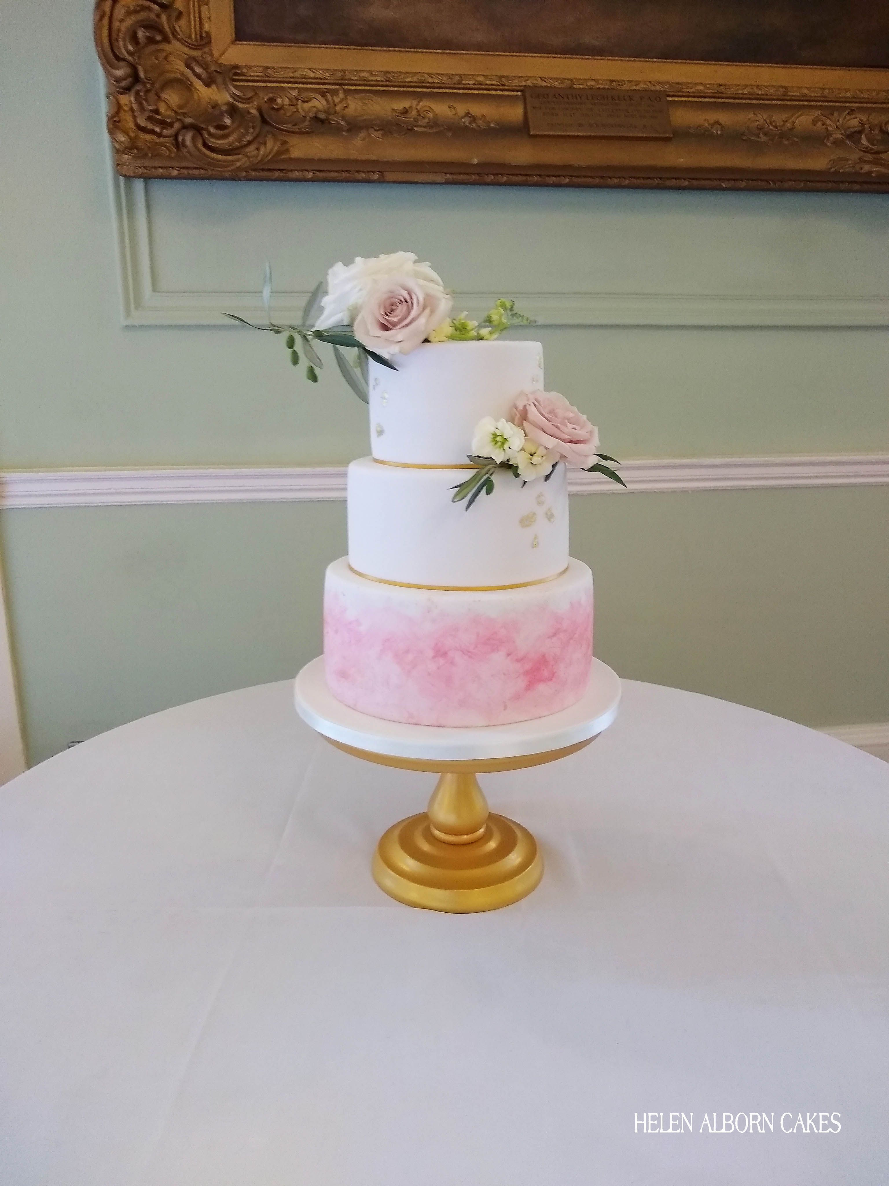 A Three Tiered Iced Wedding Cake With Hand Painted Base Tier Edible