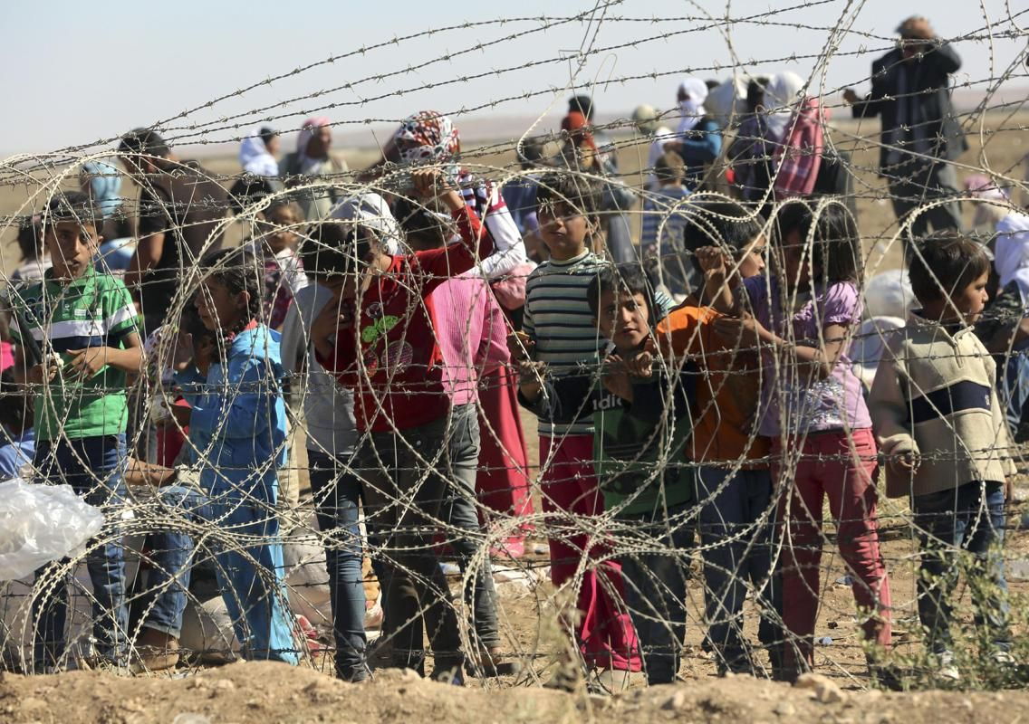 Several hundred Syrian refugees wait to cross into Turkey at the border in Suruc, Turkey, Sunday, Sept. 21, 2014.