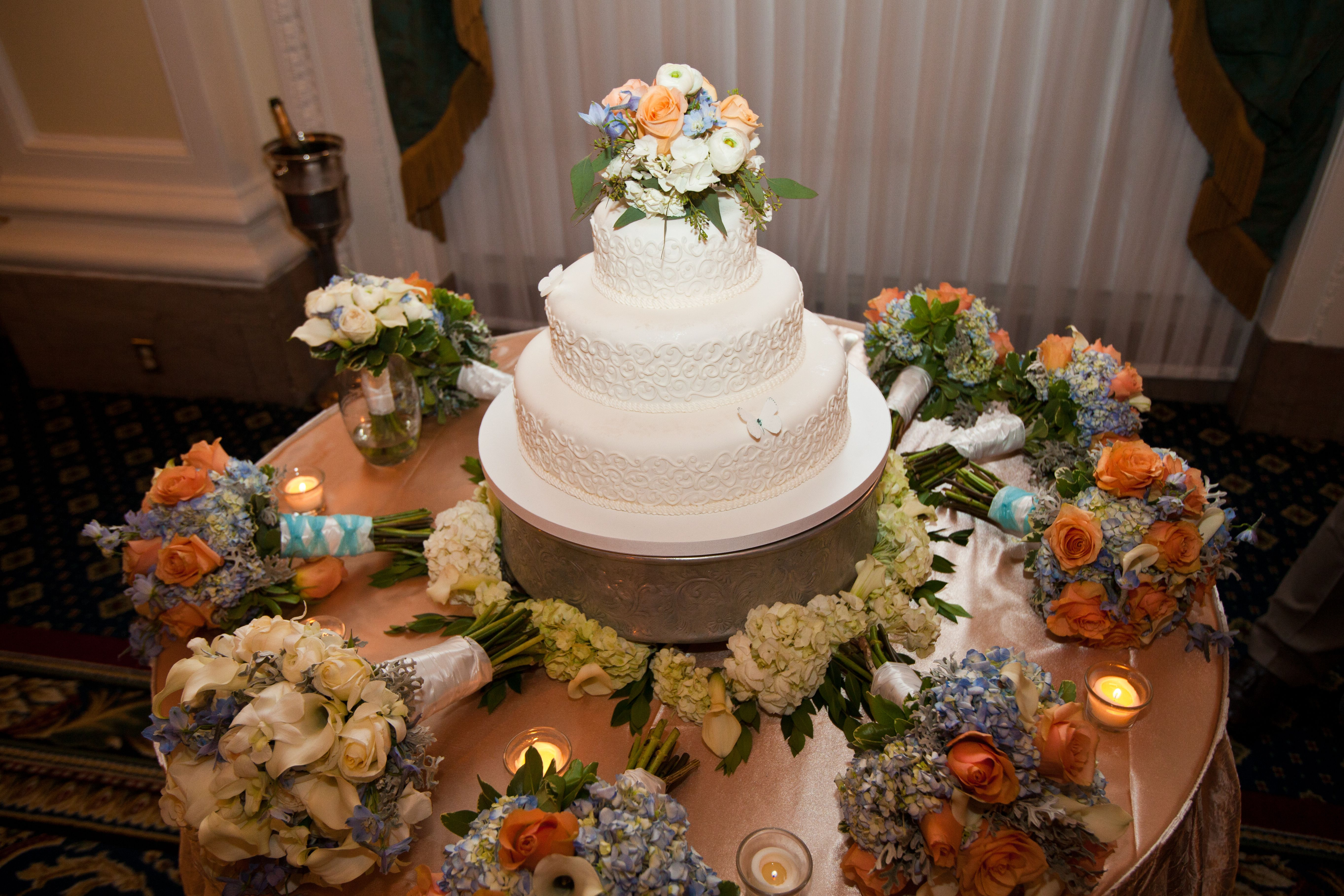 Floral cake topper and a ring of hydrangeas around the