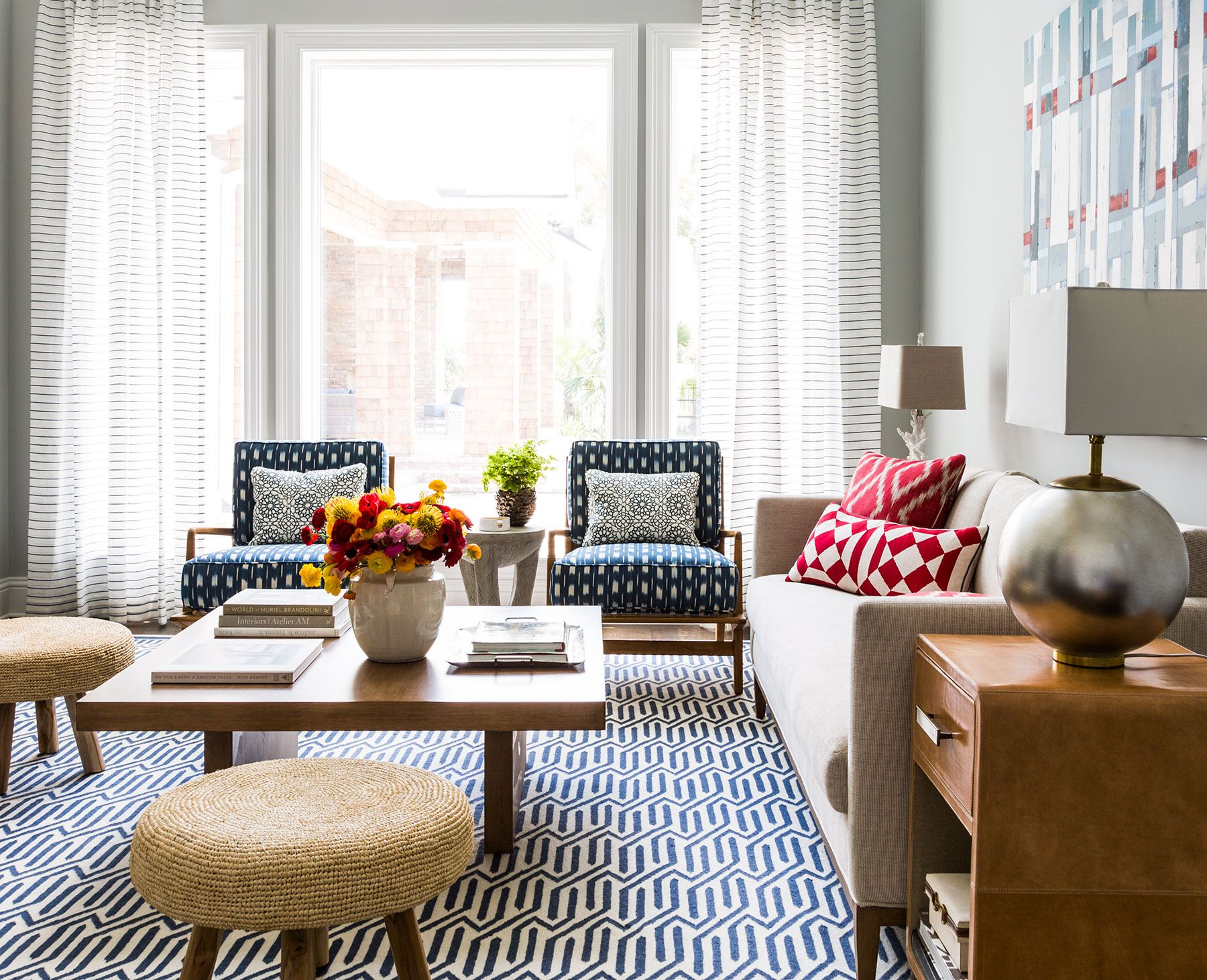 Cute living room with large patterned area rug, red accents pillows ...