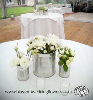 Wedding reception centerpiece arrangement of silver tin cans filled wedding reception centerpiece arrangement of silver tin cans filled with white blooms surrounded by tea light candles junglespirit Images