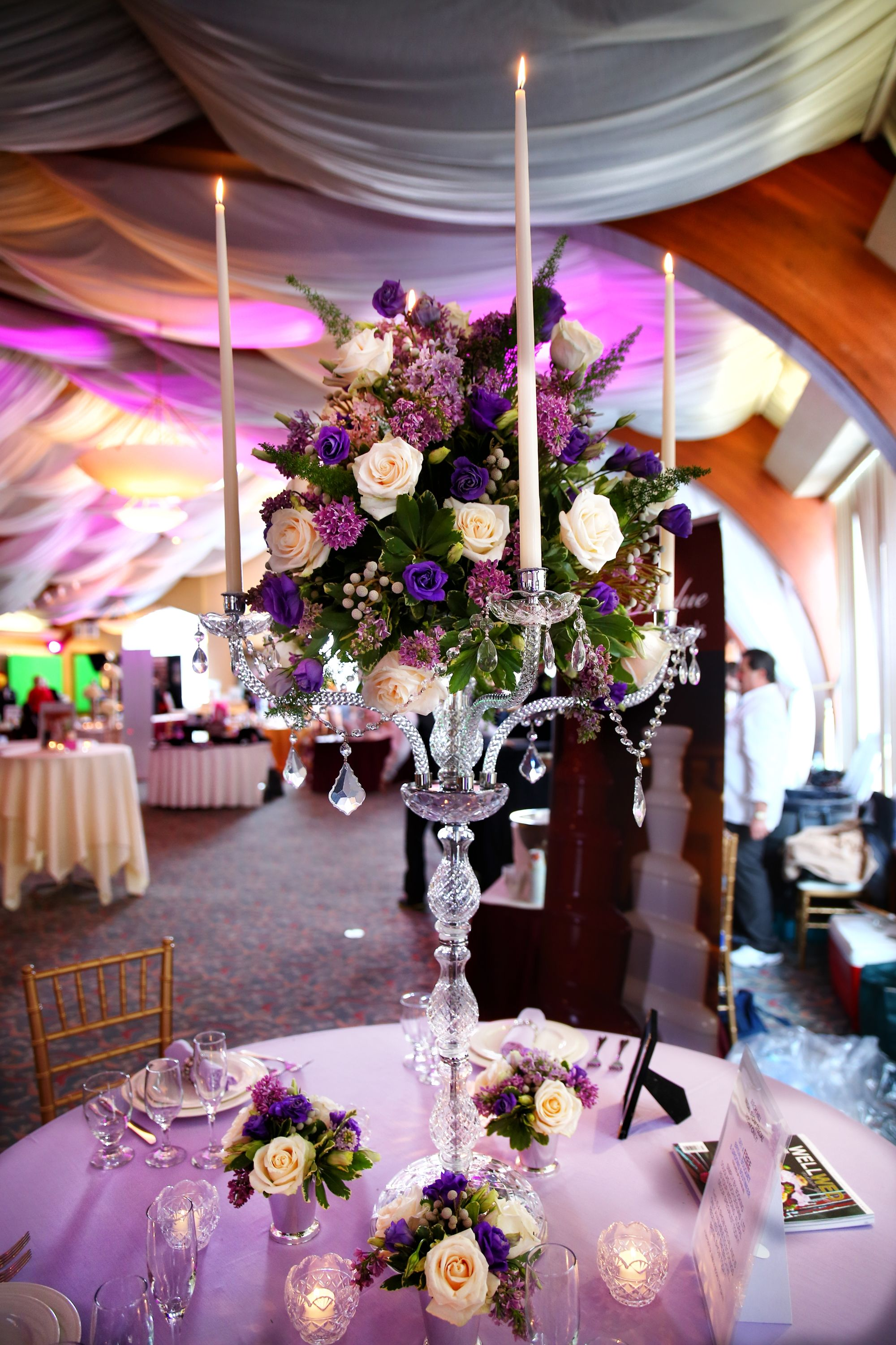 Wedding hall decoration images  tall elegant crystal candelabra with an arrangement of purple and