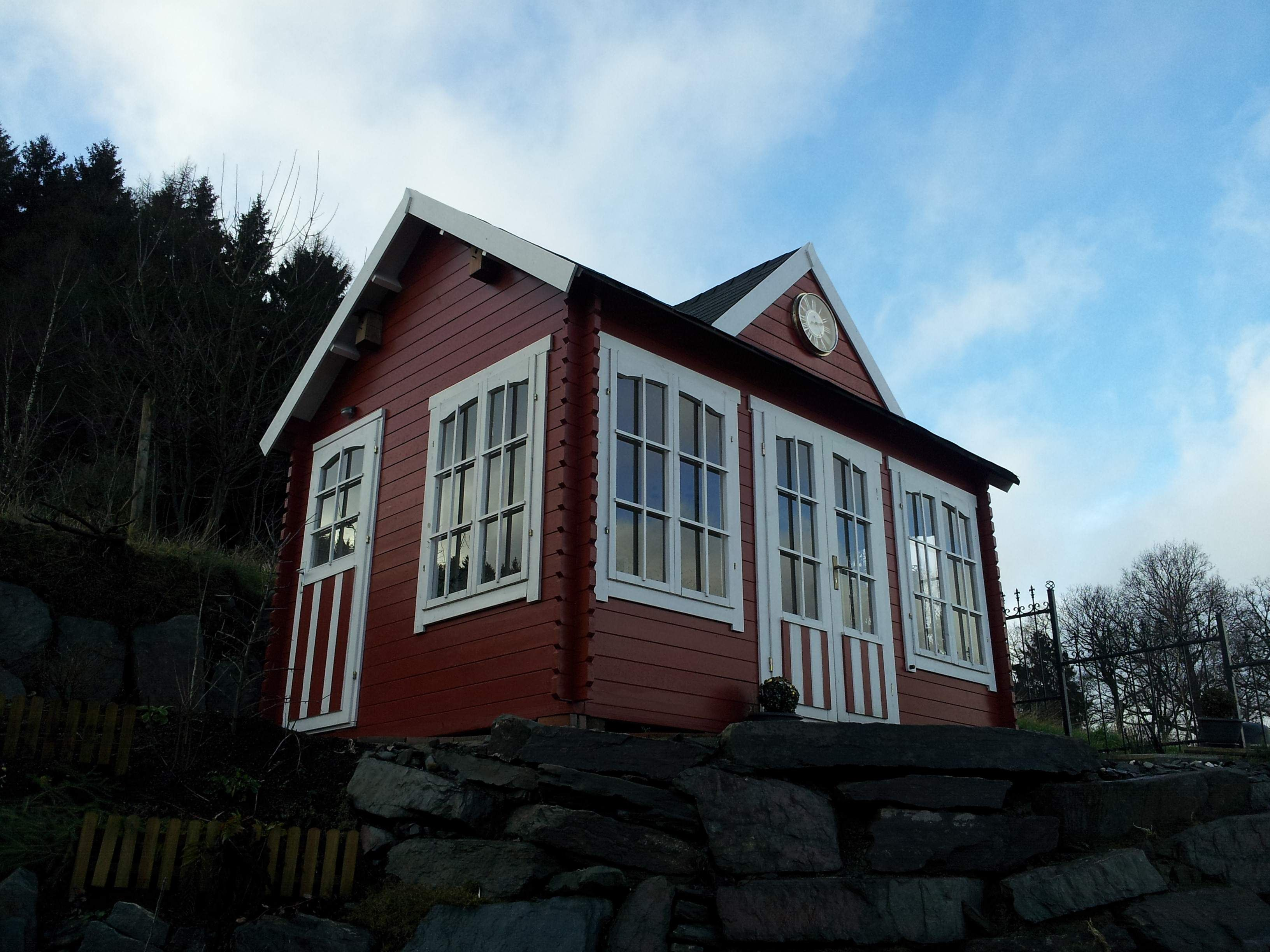 Clockhouse Gartenhaus am Steilhang in knalligem Rot. http://