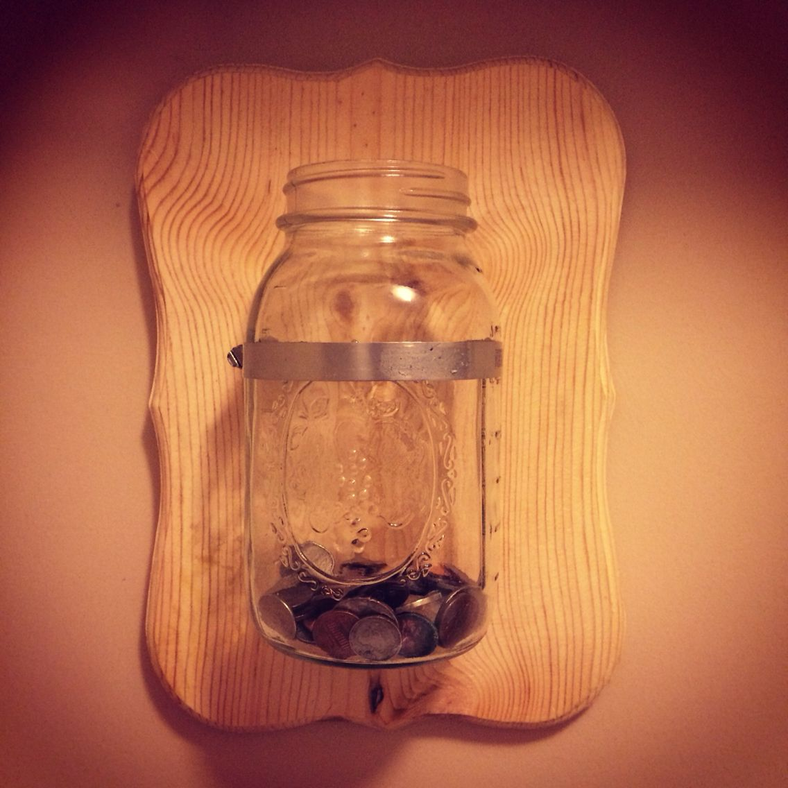 Keep the change rustic laundry room decor. Ball mason jar from goodwill: $1; wood plaque from Walmart: $4.99; metal clasp from Home Depot: $1.99