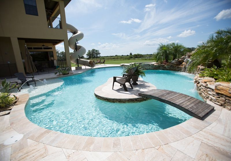 Naturalistic curved pool with tanning island and for Walk in pool designs