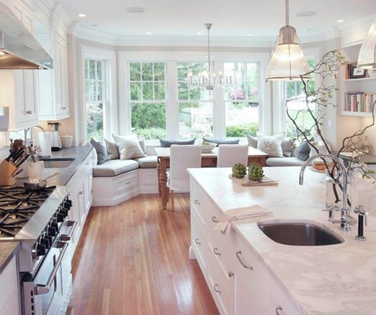 White kitchen, wood floor, marble sink counter, wide windows