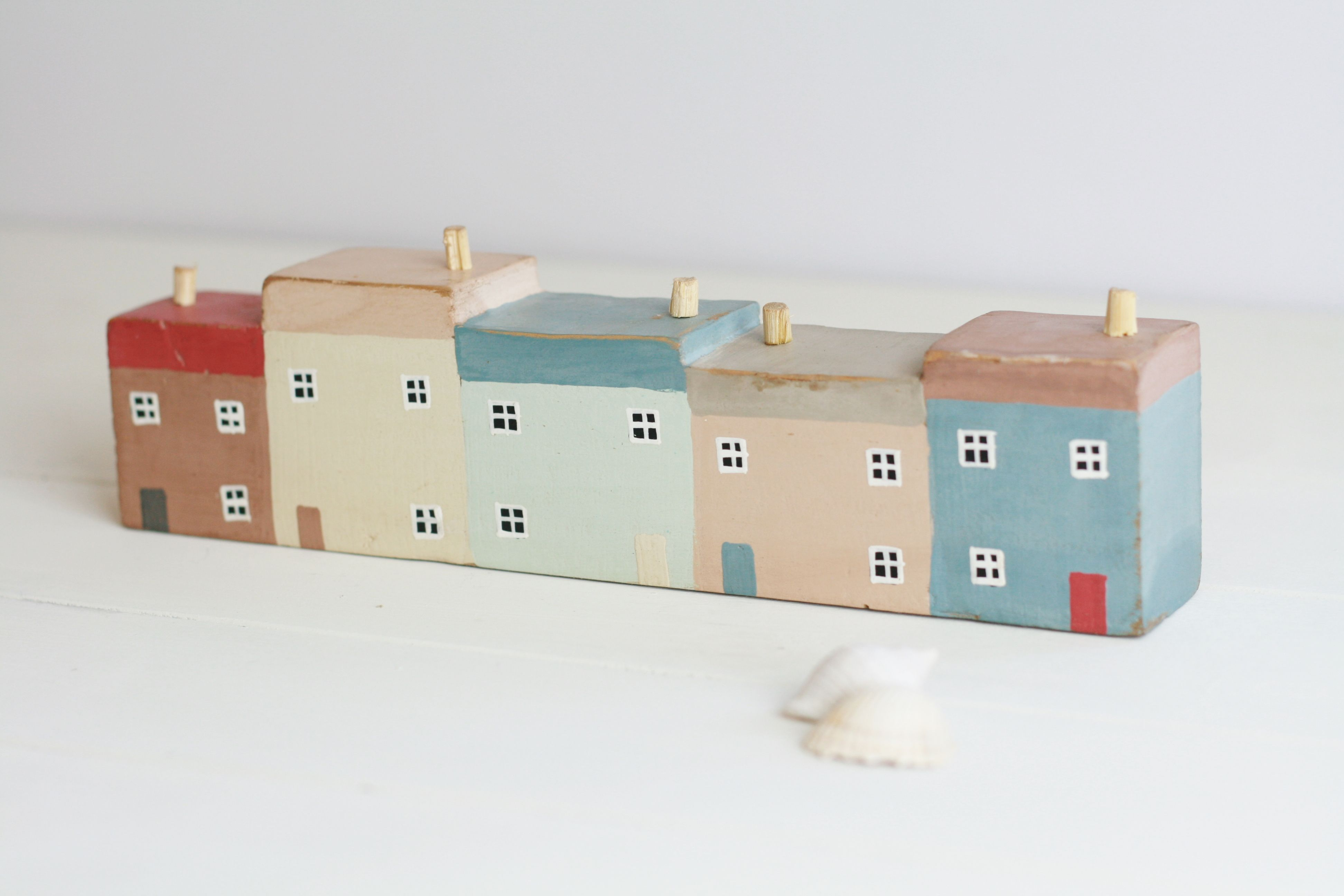 These are a lovely hand-painted row of harbour houses. They are in a chunky style wood and are painted to represent five different coloured houses all in a row. Each one has little painted windows and doors in a simplistic style with different coloured roofs and wooden chimney pots. This would make such a cute accessory on the shelf of a bathroom, or in a cottage with a nautical or seaside themed room. It would also make a great gift. Size: L25cms x H7cm x D4cms