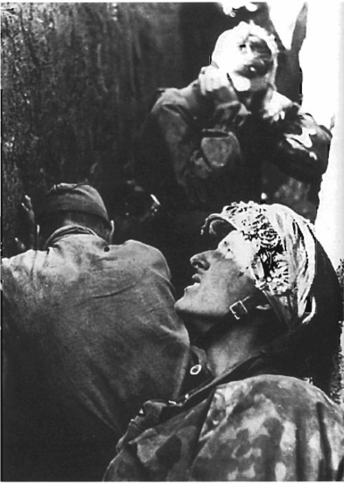 SS troops are hiding in a trench during a heavy allied bombing raid on their sector during the early days of the Normandy campaign.