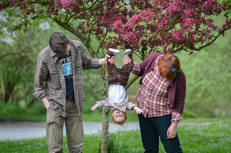 An unusual family photo pose with upside down baby