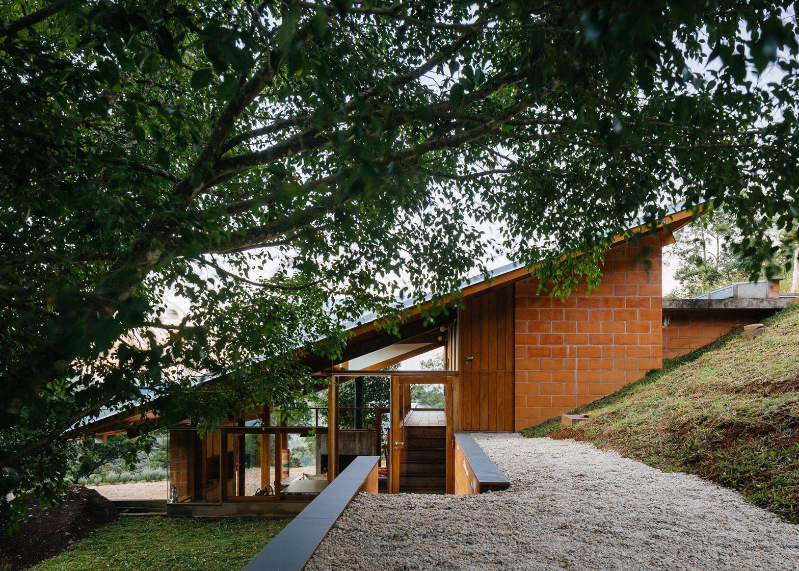 Half slope house steps into a hillside in rural brazil for Steep block home designs