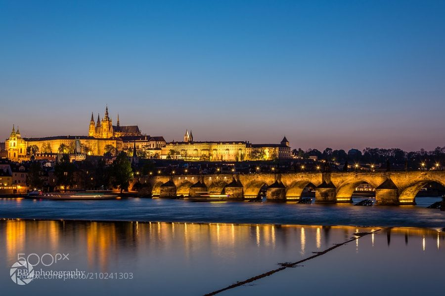 Castle of Prague and Charles Bridge at night - The lighted castle of Prague with the Charles Bridge leading to it during the blue hour.