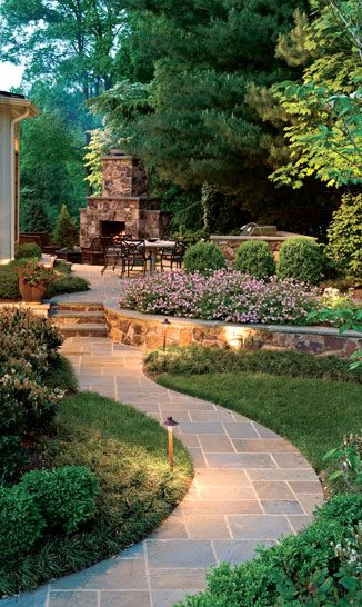Curved stone wall that warmly embraces the new entertaining area, complete with a built-in grill and fireplace that make it useable year-round. Low retaining walls provide additional seating for guests, and tall conifers add color year around.