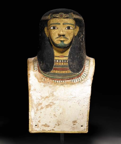 AN EGYPTIAN CARTONNAGE BUST FROM A SARCOPHAGUS Middle Kingdom, Dynasty XI-XII, 2040-1783 B.C. Depicting an official with a short mustache and beard, his wig tied with a floral fillet, wearing a necklace and broad collar, the four corners perforated for attachment, with polychromy preserved over linen and gesso 24¾ in. (62.9 cm) high