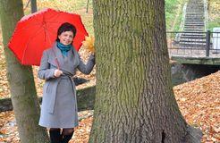 La mujer de los años medios cuesta debajo de un paraguas rojo en parque del otoño Fotografía de archivo
