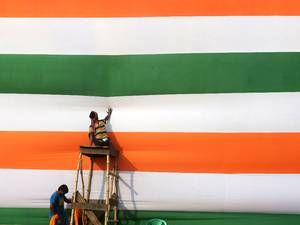 30 January 2014: Indian workers prepare a stage backdrop in the colours of their national flag ahead of the Trinamul Congress public meeting...