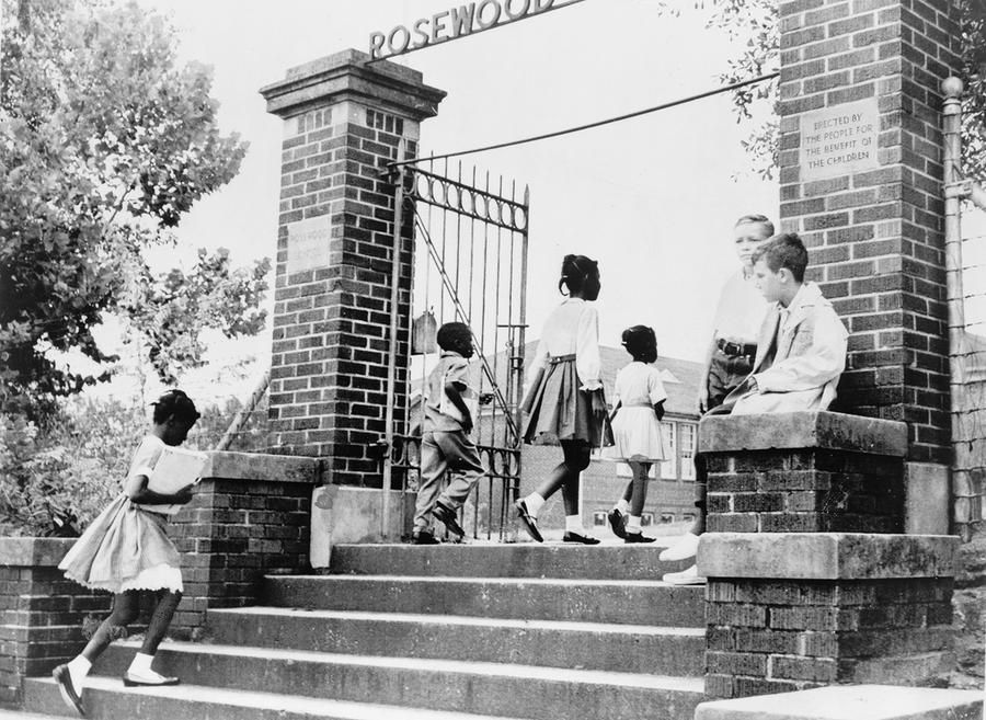 Two white students watch as African American children enter the previously all-white Rosewood Elementary School in Columbia, South Carolina, on August 31, 1964. #