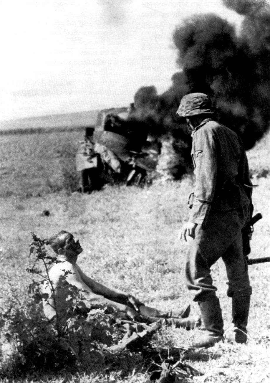 A wounded Russian soldier who managed to escapea direct hit to histanklooks helplessly up at his German captor two days after the beginning of Operation Barbarossa; the German invasion of the Soviet Union. Minsk Oblast, Belarus. 22 June 1941.