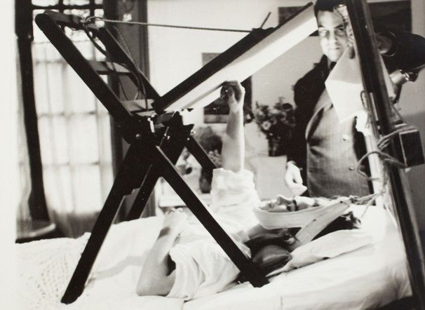 Courtesy Artisphere / Frida painting on her bed with Miguel Covarrubias at her side, 1940, Mexico City. Photographer unknown. The artist found a way to work, even while in traction. She used a device that allowed her to look up and draw and paint, and affixed a strong light to help her do so. Covarrubias, a Mexican painter and influential caricaturist, was a longtime friend of Kahlo and Diego Rivera.
