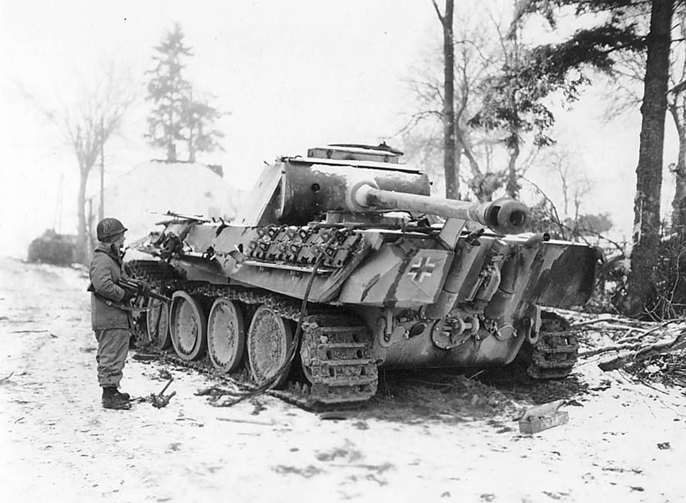 An American soldier & his Thompson SMG observe an abandoned German Panther tank in winter. Notice how much slack is in the left hand track & the road wheel appears damaged.