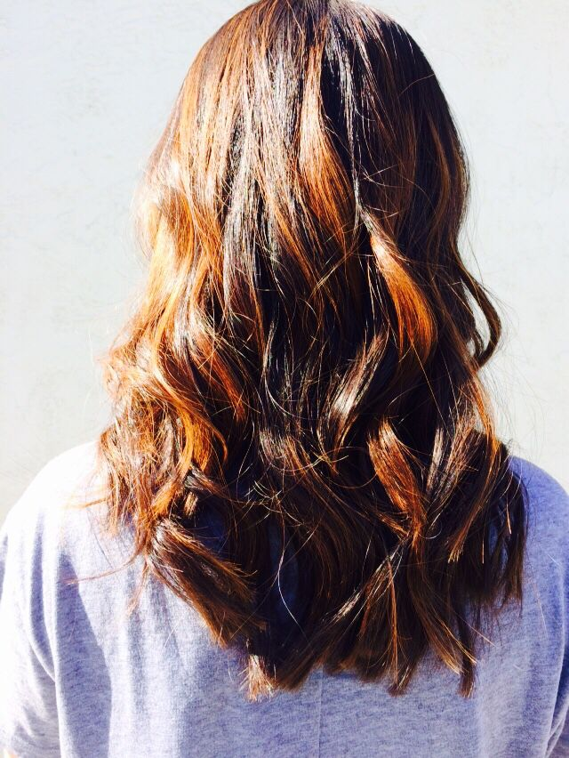 A sun kissed balayage look for dark hair with effortless waves.