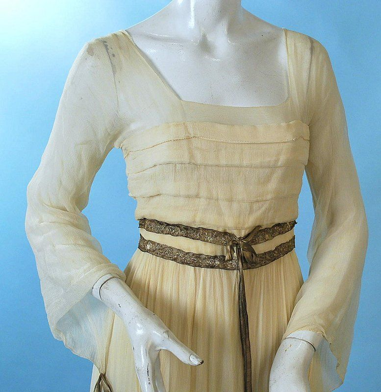 "Antique 1910 Cream Chiffon Neoclassical Fancy Dress. Horizontal pleated front of the bodice with sheer double layer through shoulders and the romantic bell sleeves. Metallic ribbon and bow trimming at waist with 3 graceful full layers of tiered chiffon in the skirting, the under layer of chiffon has a wide flounce of metallic gold lace. Back hook and eye closure with cream silk lining. Labelled on the waist petersham ""Miss Nelson Inc. Gowns, Boston"". Detail"