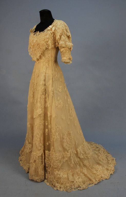 TRAINED LACE on NET WEDDING GOWN, EARLY 20th C. Boned bodice with short puffed sleeve gathered into a wide band trimmed with ribbon and two rhinestone circles, open neck and back with rhinestone and bow details, full skirt with double scalloped hem, decorated with lace swags, medallions and floral sprays, lined in cream taffeta, back hook & eye closures. Front