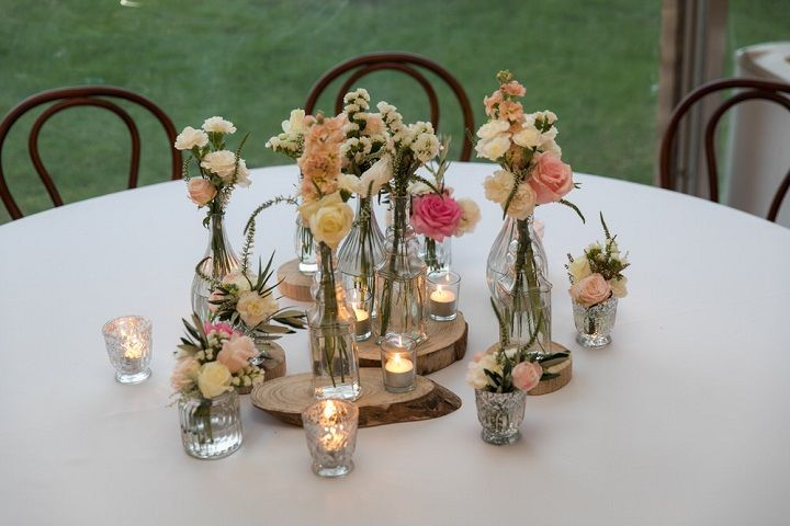 Bottle filled in with flowers Wedding centerpiece | Beautiful garden styled wedding | itakeyou.co.uk #gardenwedding #sophiatolli #weddingdress #outdoorwedding #weddingreception