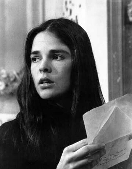 """Ali MacGraw reading a letter in Love Story (1970). Roger Ebert defined """"Ali MacGraw's Disease"""" as a movie illness in which """"the only symptom is that the patient grows more beautiful until finally dying."""" He also said """"Ali MacGraw and Ryan O'Neal, who play the lovers on film, bring them to life in a way the novel didn't even attempt. They do it simply by being there, and having personalities."""""""