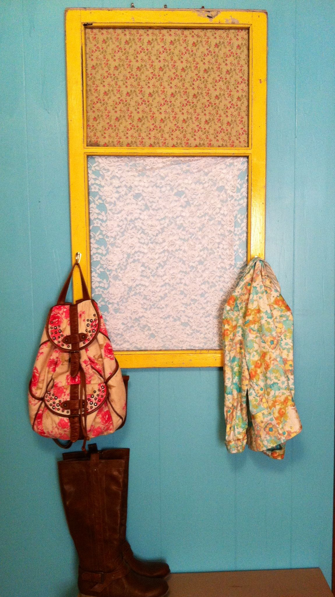 Found an old window frame in my basement. Distressed the yellow paint attached hooks, stapled fabric in the back on top and lace in the bottom. Super cute and vintage!!!
