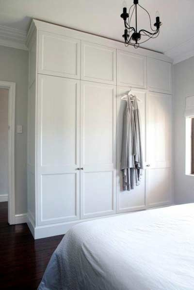 Built in wardrobe next to door frame, leaving space for light switch: