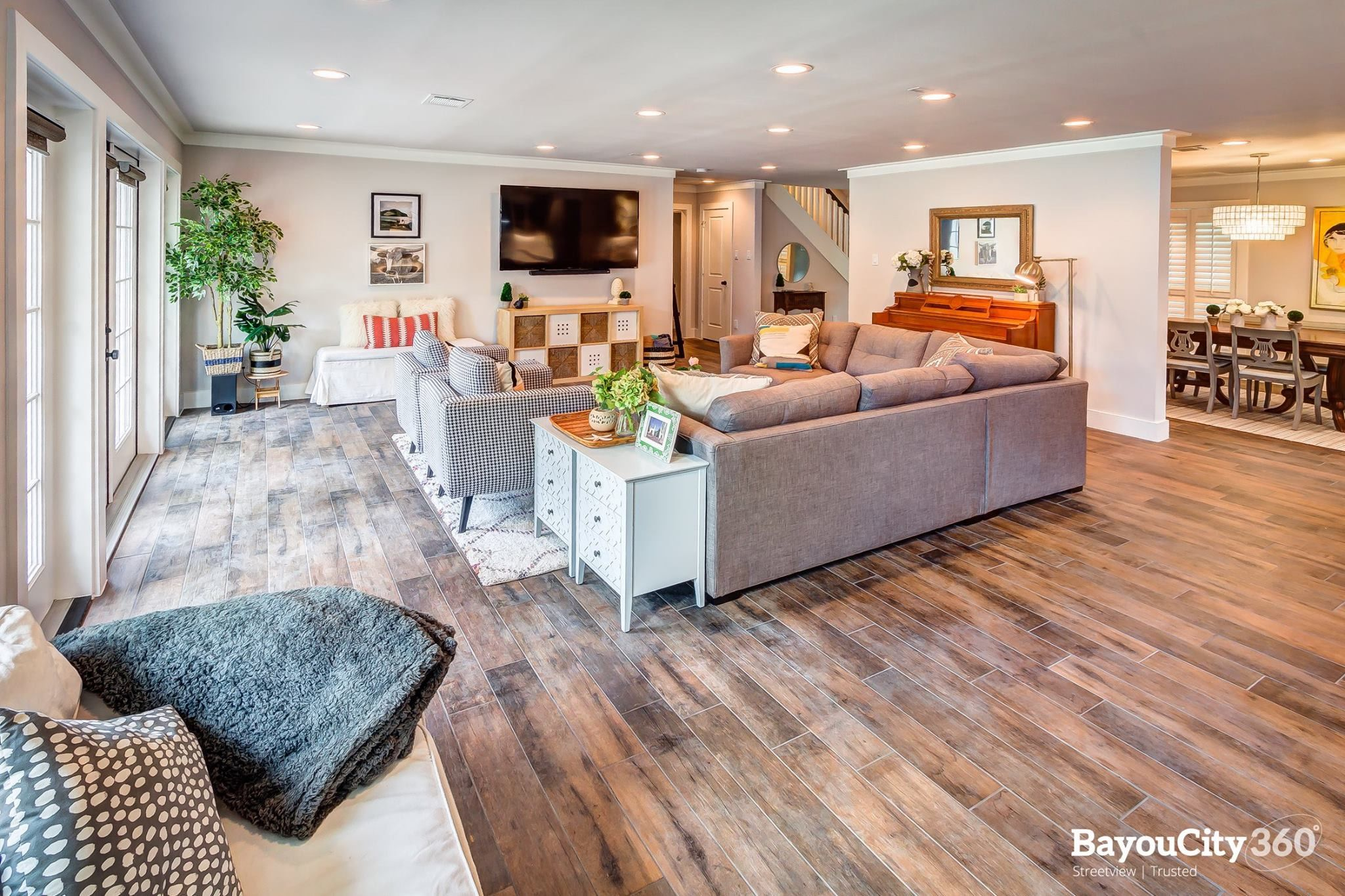 Living room with large tv and plants. Wood look tile. Eider white walls.  Flat trim and molding. Eclectic style. … | Living room tv, Living room tv  wall, Living room