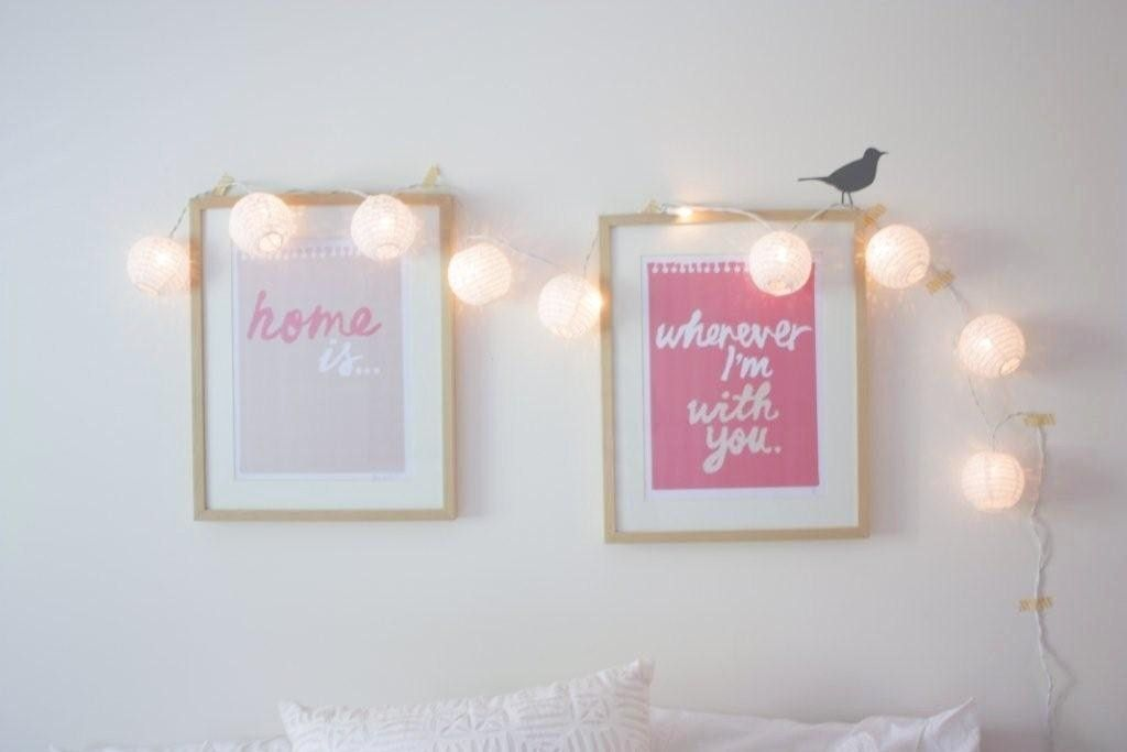 Lights hanging over picture frames.