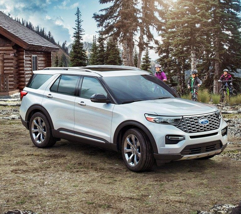 2020 Explorer Platinum In Iconic Silver Shown In Front Of A Cabin