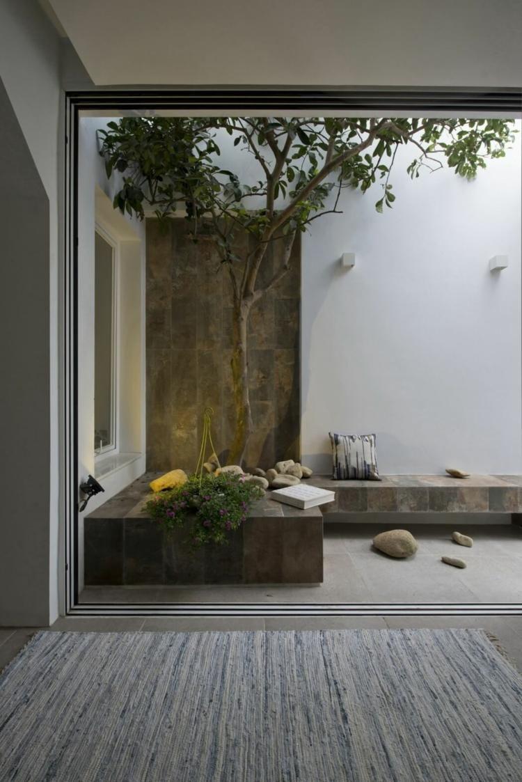 Eingebaute Sitzbank und Mini-Garten mit Baum auf einer Dachterrasse ...