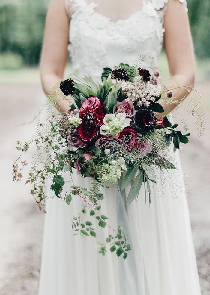 A wedding bouquet featuring rich reds and textural ferns.