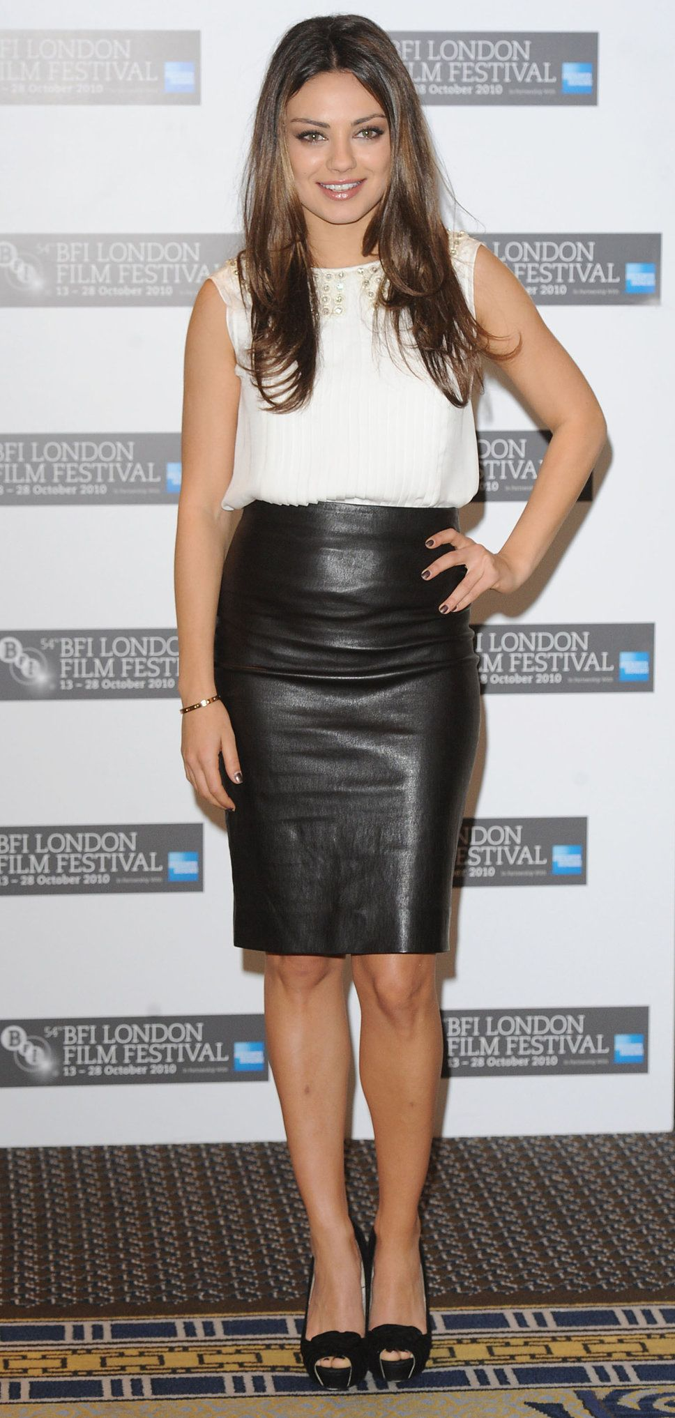Mila Kunis black leather skirt white tank top black peep toe ...
