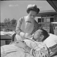 "SANATORIUM NURSING: EVERYDAY LIFE AT BROOMFIELD SANATORIUM, CHELMSFORD, ESSEX, ENGLAND, 1945 part of ""MINISTRY OF INFORMATION SECOND WORLD WAR OFFICIAL COLLECTION"" (photographs) Made by: Ministry of Information Photo Division Photographer A nurse uses a spouted cup to feed a patient in the sunshine of an open air 'ward' of Broomfield Sanatorium, Chelmsford. This patient has been ordered complete bed rest, and so cannot sit up to drink."