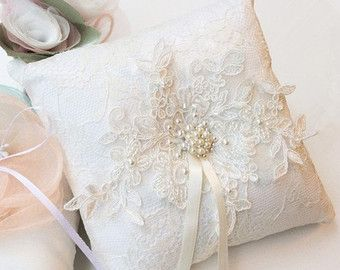 White ring pillow decorated with lace and pink satin rose ring